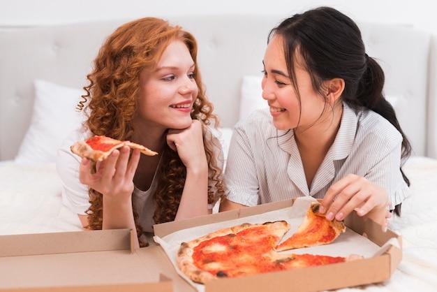 Hohe winkelsmileyfrauen, die pizza essen