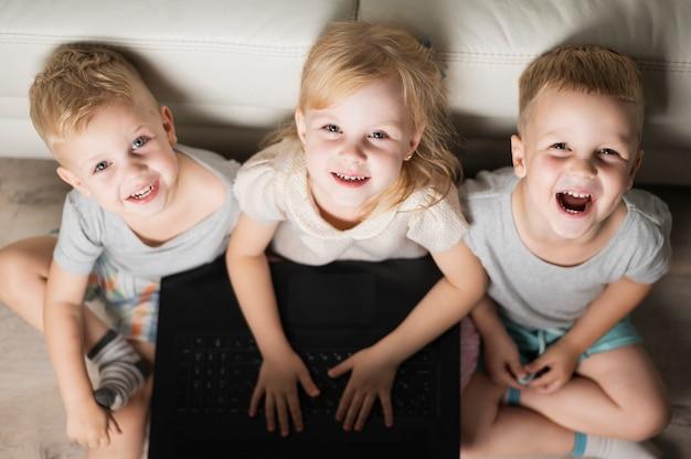 Hohe winkelsmileygeschwister, die auf laptop spielen