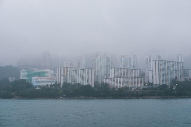 Hohe wolkenkratzer aus grauem beton an der küste bei nebligem wetter