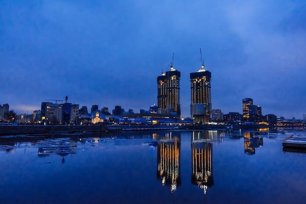 Hohe wolkenkratzer in moskau spiegelten sich nachts im wasser