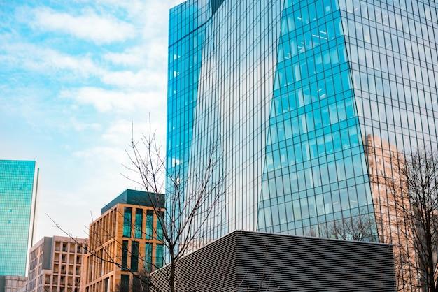 Hohe wolkenkratzer und niedrige gebäude mit glasfenstern in der stadt. geschäftszentrum