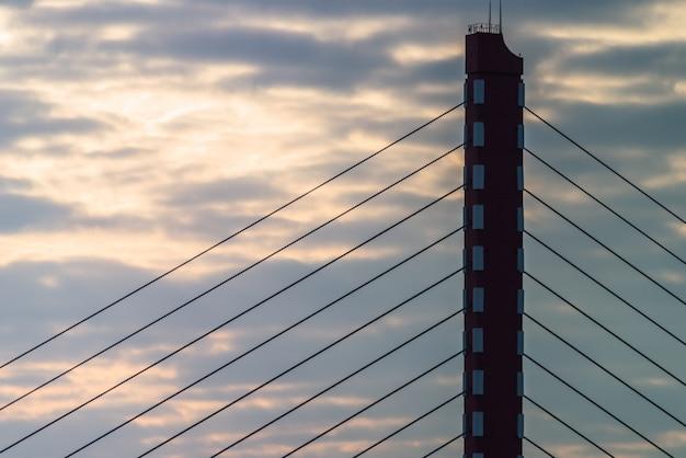 Hoher abschnitt eines modernen kabels blieb brücke am himmel hintergrund
