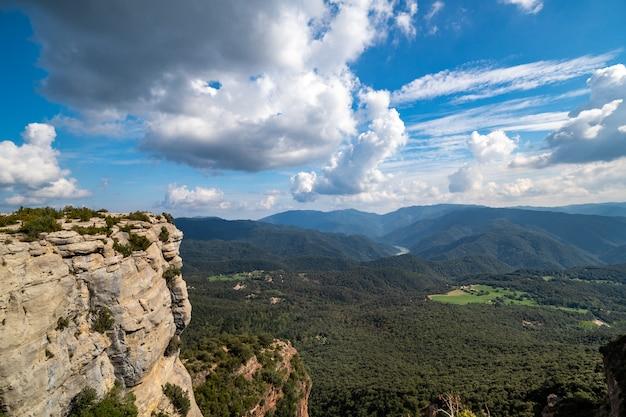 Hoher felsen mit blauem himmel und grünem wald, tavertet, katalonien.