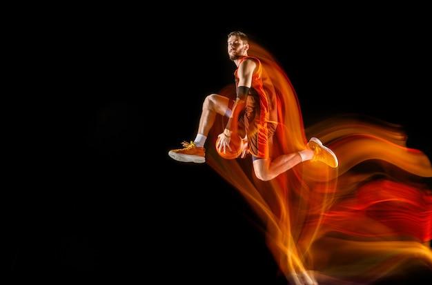 Hoher flug. junger kaukasischer basketballspieler der roten mannschaft in aktion