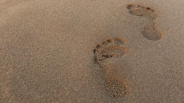 Hoher fußabdruckwinkel im sand am strand