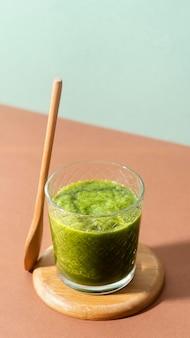 Hoher grüner smoothie und holzlöffel
