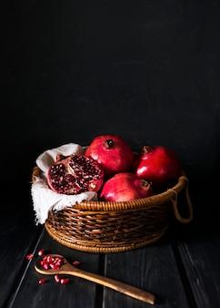 Hoher korbwinkel mit herbstlichen granatäpfeln und kopierraum