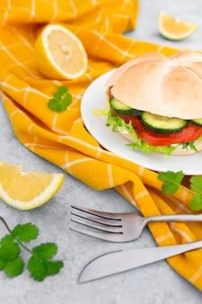 Hoher sandwichwinkel auf teller mit besteck und zitronenscheiben