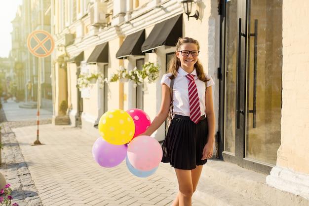 Hoher schüler des mädchenjugendlichen mit ballonen