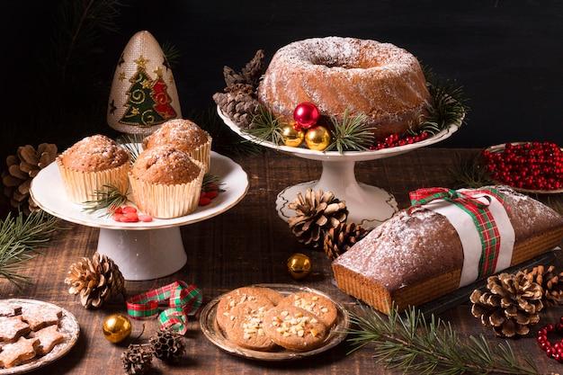 Hoher sortimentswinkel von weihnachtsdesserts mit tannenzapfen und roten beeren