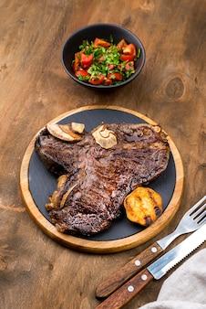 Hoher steakwinkel mit salat und besteck