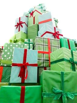 Hoher turm aus weihnachtsgeschenkboxen, bedeckt mit schönem grünem papier mit roten bändern in der halle des einkaufszentrums