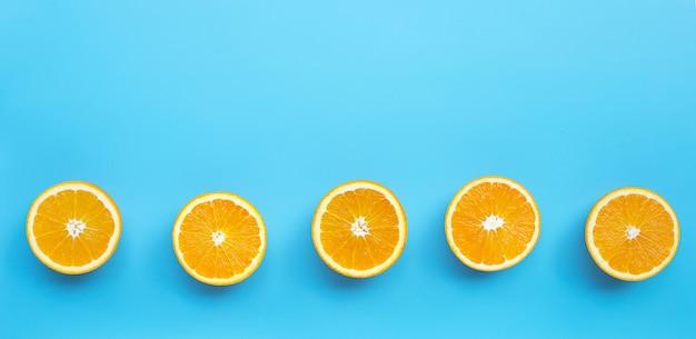 Hoher vitamin c, saftig und süß. frische orangenfrucht auf blauem hintergrund.