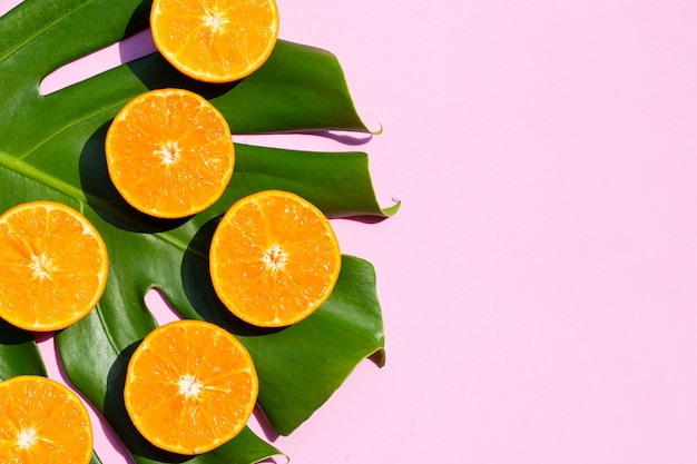 Hoher vitamin c, saftig und süß. frische orangenfrucht mit monstera-pflanzenblatt auf rosa hintergrund.