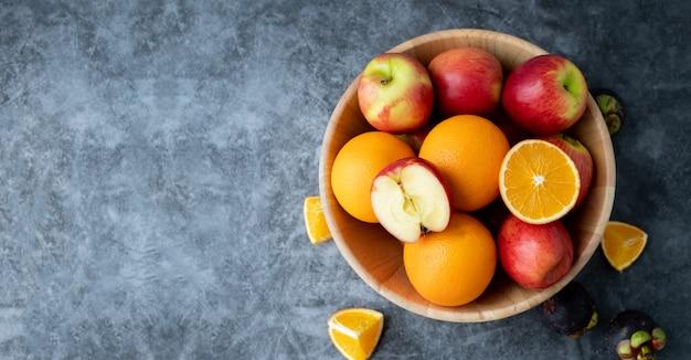 Hoher vitamin c trägt auf hölzerner platten-, apfel- und orangenfrucht früchte.
