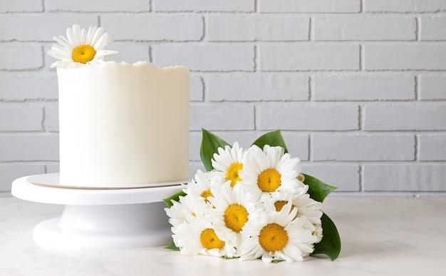 Hoher weißer kuchen auf einem ständer und einem strauß gänseblümchen.