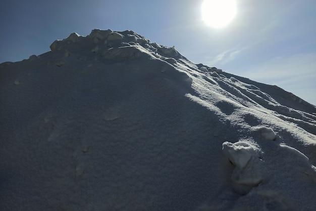 Hoher weißer schneehaufen am sonnigen wintertag.