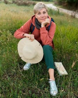Hoher winkel der älteren touristenfrau in der natur mit hut