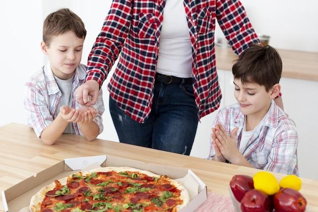 Hoher winkel der arten, die ihre hände desinfizieren, bevor sie pizza essen