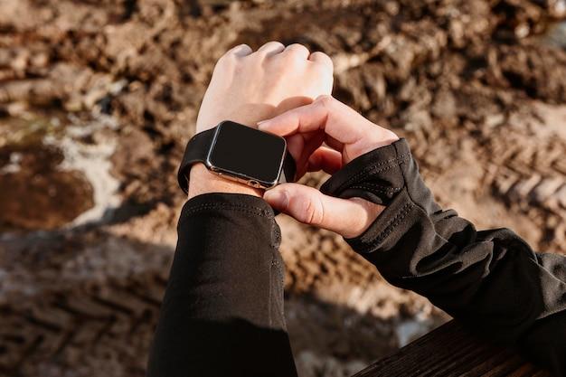 Hoher winkel der athletischen frau, die ihre smartwatch repariert