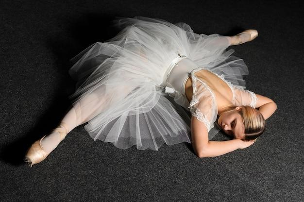 Hoher winkel der ballerina aufwerfend beim handeln einer spalte im ballettröckchenkleid
