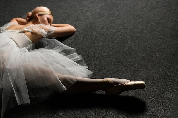 Hoher winkel der ballerina im ballettröckchenkleid, das eine spalte tut