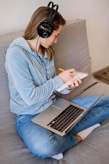 Hoher winkel der frau auf der couch, die notizen vom online-unterricht macht