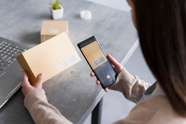 Hoher winkel der frau, die barcode auf box mit smarphone scannt