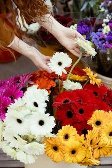 Hoher winkel der frau, die frühlingsblumen bewundert