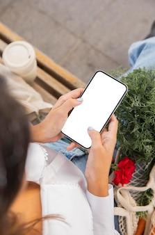 Hoher winkel der frau, die ihr smartphone im freien verwendet