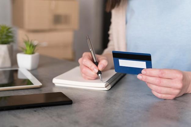 Hoher winkel der frau, die kreditkarte hält und auf notizblock schreibt