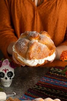 Hoher winkel der frau, die pan de muerto mit sahne hält