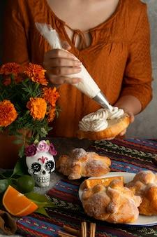 Hoher winkel der frau, die pan de muerto mit sahne verziert