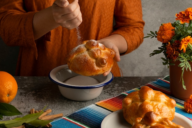 Hoher winkel der frau, die pan de muerto mit zucker verziert