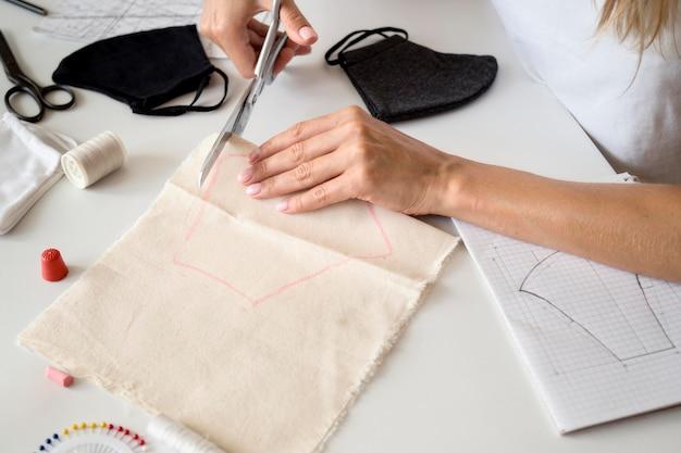 Hoher winkel der frau, die textil schneidet, um gesichtsmaske zu nähen