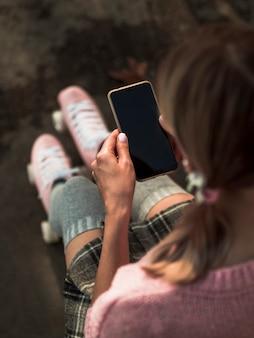 Hoher winkel der frau in den rollschuhen, die smartphone halten