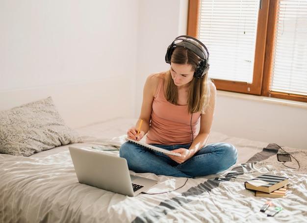 Hoher winkel der frau mit kopfhörern im bett, die eine online-klasse haben