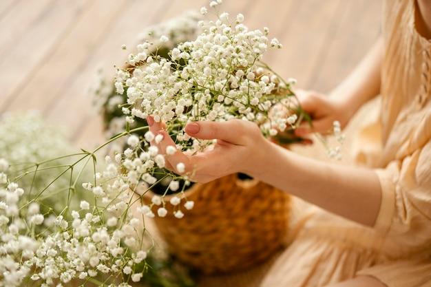 Hoher winkel der frau mit korb der zarten frühlingsblumen