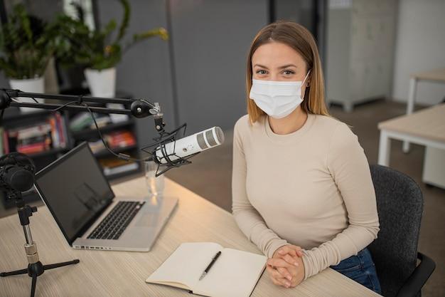 Hoher winkel der frau mit medizinischer maske im radiostudio