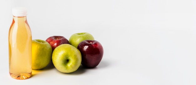 Hoher winkel der fruchtsaftflasche mit äpfeln