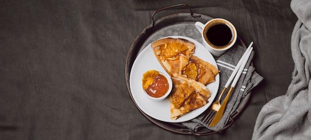 Hoher winkel der frühstücks-crepes mit marmelade und kopierraum