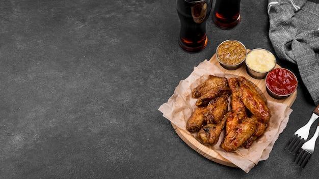 Hoher winkel der gebratenen hühnerflügel mit einer vielzahl von saucen und kohlensäurehaltigen getränken