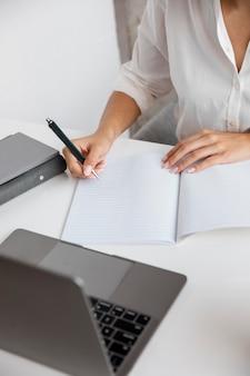 Hoher winkel der geschäftsfrau, die mit notebook und laptop arbeitet
