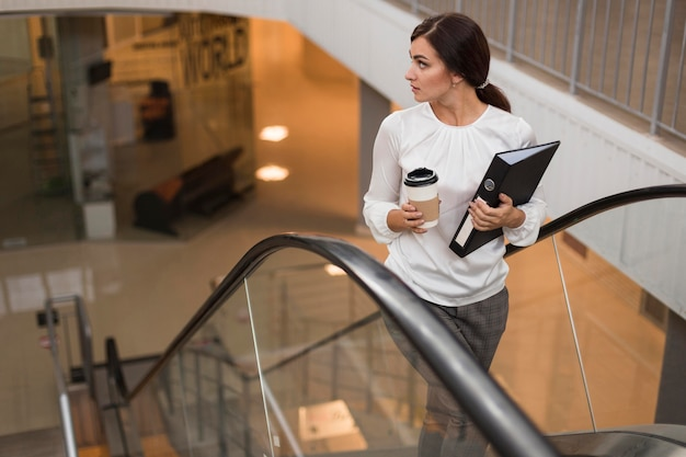 Hoher winkel der geschäftsfrau mit binder und kaffee auf rolltreppe