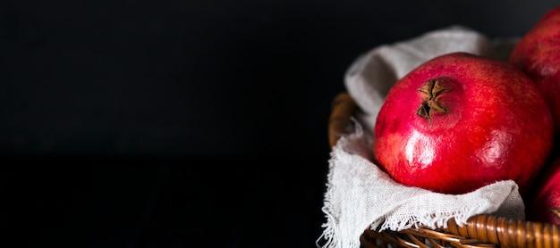 Hoher winkel der granatäpfel im korb mit kopierraum