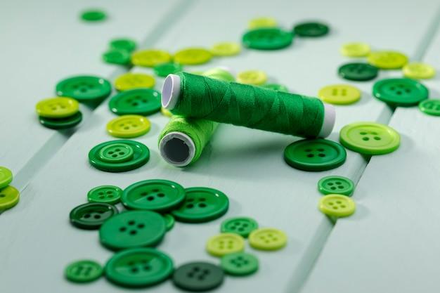 Hoher winkel der grünen garnrollen und knöpfe