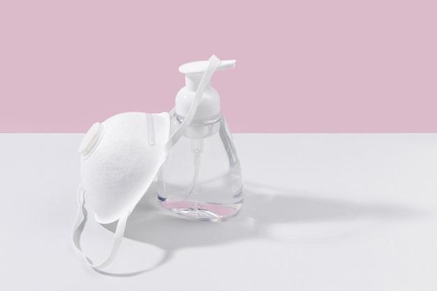 Hoher winkel der händedesinfektionsflasche mit gesichtsmaske und kopierraum