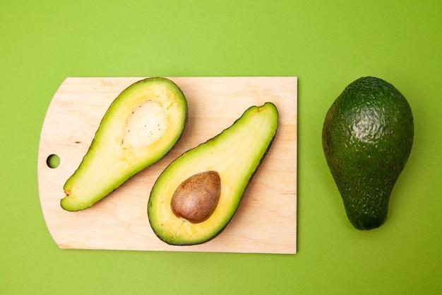 Hoher winkel der halbierten avocado mit samen auf holzbrett in der nähe von ganzen früchten auf grünem hintergrund