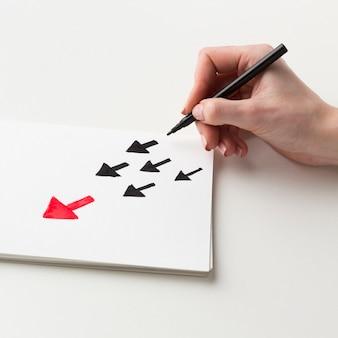 Hoher winkel der hand, die pfeile auf papier zeichnet