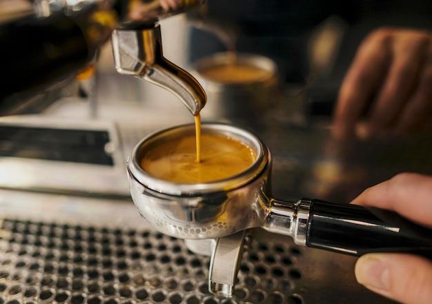 Hoher winkel der kaffeemaschinenschale von barista gehalten